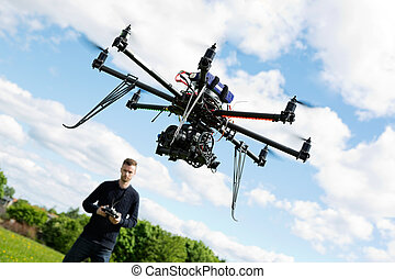 Technician Flying UAV Helicopter in Park - Young technician...