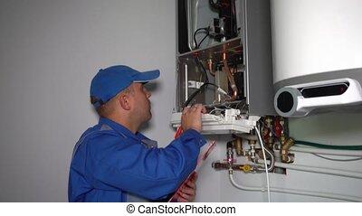 Technician inspector inspecting maintenance gas boiler ...