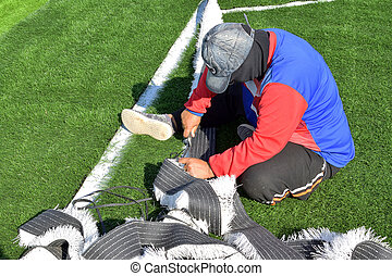Technician is working on artificial turf.