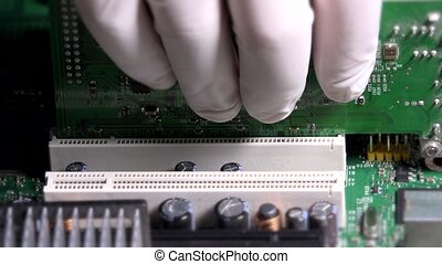 Technician man hands with gloves removing card from computer main board