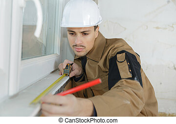 technician measuring the window frame with a measuring tape