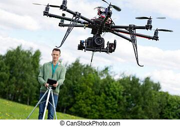 Technician Operating UAV Octocopter - UAV octocopter flying...