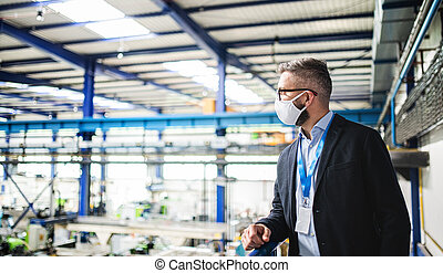 Technician or engineer with protective mask standing in industrial factory.