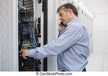 Technician phoning while repairing a server - Technician...