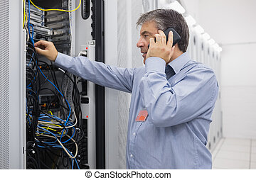 Technician phoning while repairing the server - Technician...