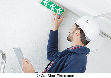 technician placing an emergency exit sign