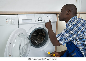 Technician Pressing Button On Washing Machine
