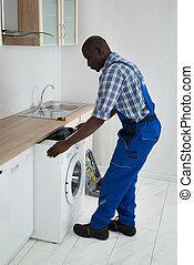 Technician Pulling Washing Machine In Kitchen