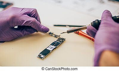 Technician repair microchip and motherboard of mobile phone in electronic smart phone technology service. Cellphone technology device maintenance engineer