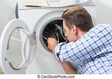 Technician repairing a washing machine - Side view of a...