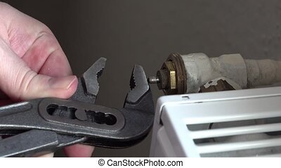 Technician repairing heating Thermostat pliers.