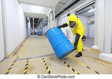 technician in uniform rolling barrel with hazardous substance