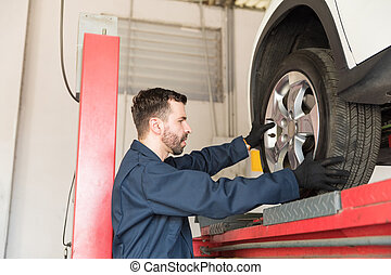 Technician Servicing Car On Lift In Garage