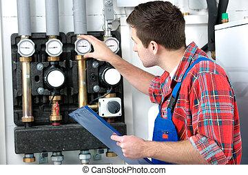 Technician servicing heating boiler - Technician servicing...