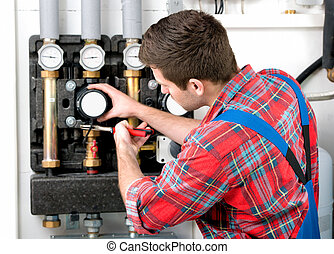 Technician servicing heating boiler