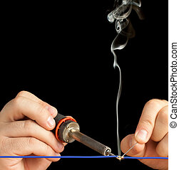 Soldering Tech soldering a blue wire on a pure black background.
