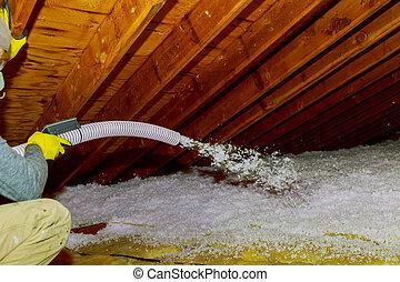 Technician spraying blown Fiberglass Insulation between Attic Trusses foam insulation construction foam from the gun to the roof