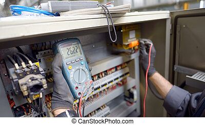 Technician testing a control panel