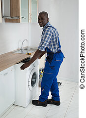 Technician With Washing Machine In Kitchen