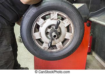 Technician work with mechanic balancing wheel