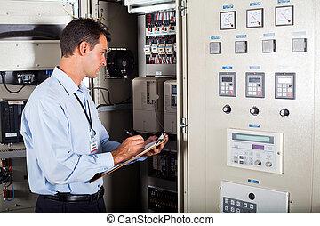 technician writing down machine data - technician writing...