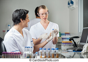 Technicians Analyzing Sample In Medical Lab