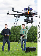 Technicians Flying UAV Helicopter in Park - Young...