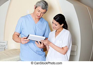 Multiethnic radiologic technicians looking at clipboard while standing by CT scan machine