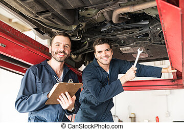 Technicians Smiling While Under Car In Garage