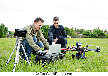 Technicians Using Laptop By Tripod And UAV - Young male...