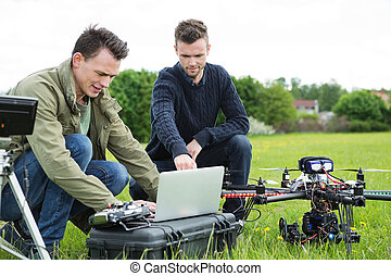 Technicians Using Laptop By UAV Drone - Young technicians...