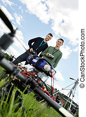 Technicians With Remote Controls Of UAV