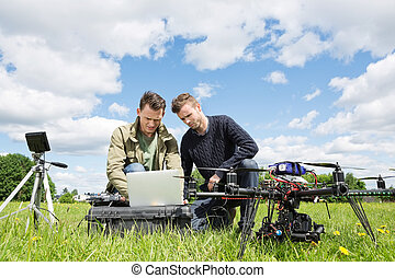 Technicians Working On Laptop By UAV in Park