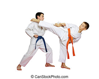 Technique karate in perform athletes with orange and blue belt