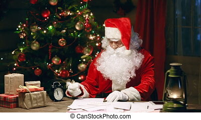 Santa Claus finishing his reply letter and browsing digital tab