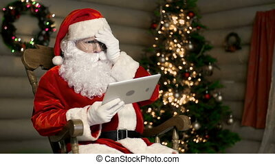 Technological Wonder - Santa Claus using digital tablet and...