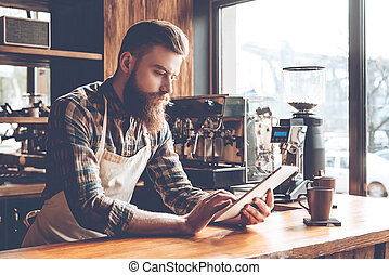 Technologies make business easier. Young bearded man in apron using his digital tablet while leaning to bar counter at cafe