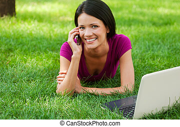 Technologies making life easier. Attractive young woman talking on the mobile phone and smiling while lying in grass with laptop laying near her