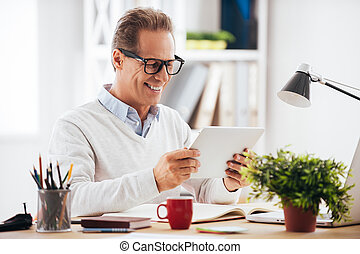 Technologies making life easier. Cheerful mature man holding digital tablet and looking at it with smile while sitting at his working place