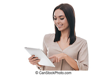 Technologies making life easier. Confident young woman in smart casual wear holding digital tablet and looking at it with smile while standing against white background