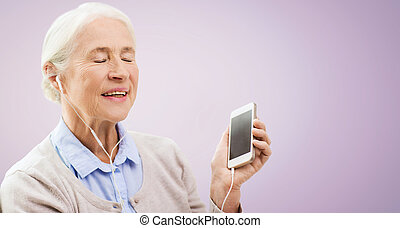 senior woman with smartphone and earphones - technology, age...