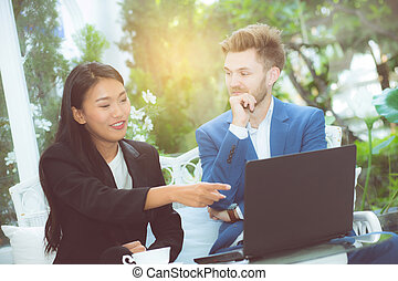 technology and office concept - two business man and woman with laptop - tablet pc computer and papers having discussion in office.
