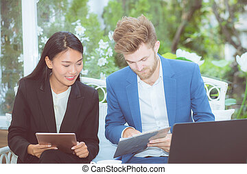 technology and office concept - two business man and woman with laptop - tablet pc computer and clipboard document having discussion in office.