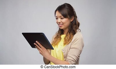 asian woman using tablet computer - technology and people...