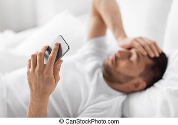 hand of young man with smartphone in bed