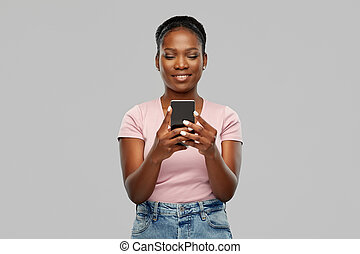 happy african american woman using smartphone