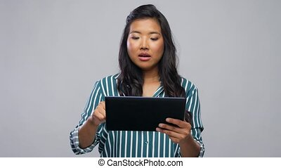 technology and people concept - happy asian woman using tablet computer over grey background
