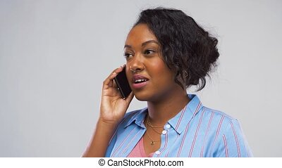 happy african american woman calling on smartphone -...