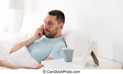 man calling on smartphone in bed at home - technology,...