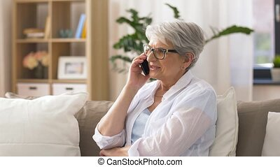 senior woman calling on smartphone at home - technology,...